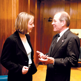 A woman and a man in suits talking to each other.