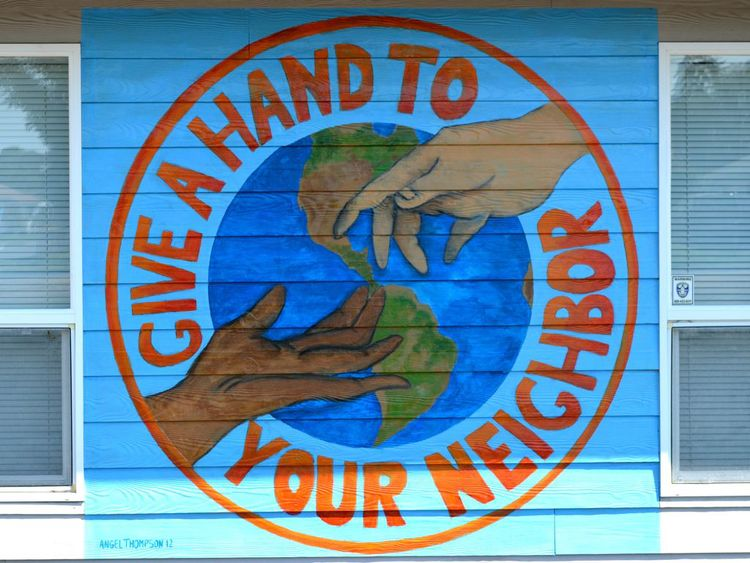 "Mural reading, ""Give a hand to your neighbor."""