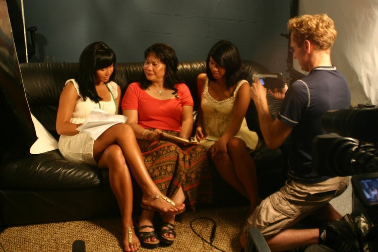 Three Cambodian women sit on a couch in front of a cameraman.