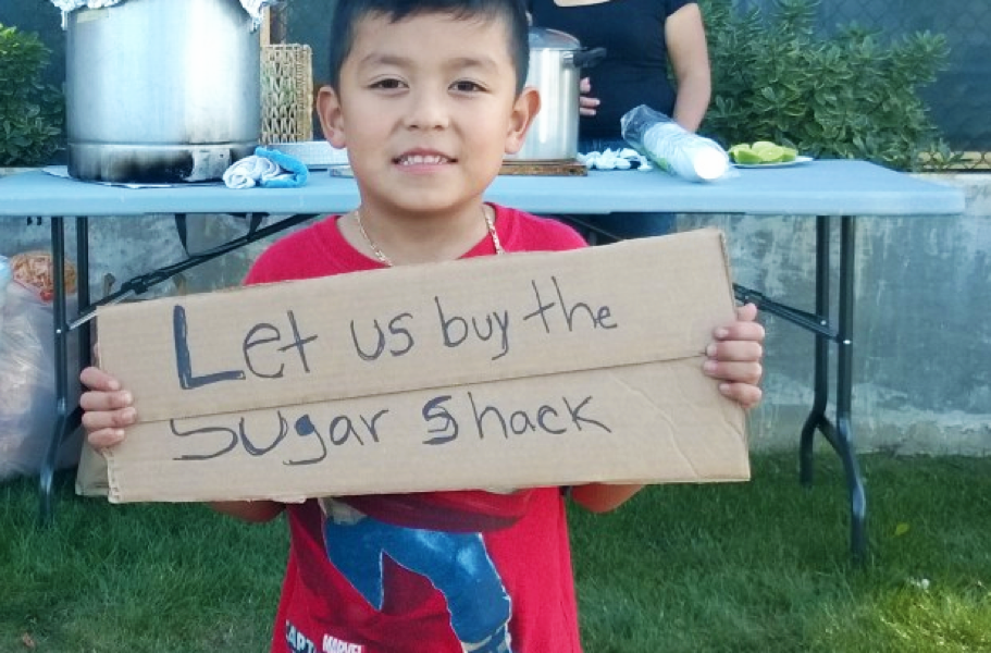 "A little boy holds a sign that says, ""Let us buy the Sugar Shack."""