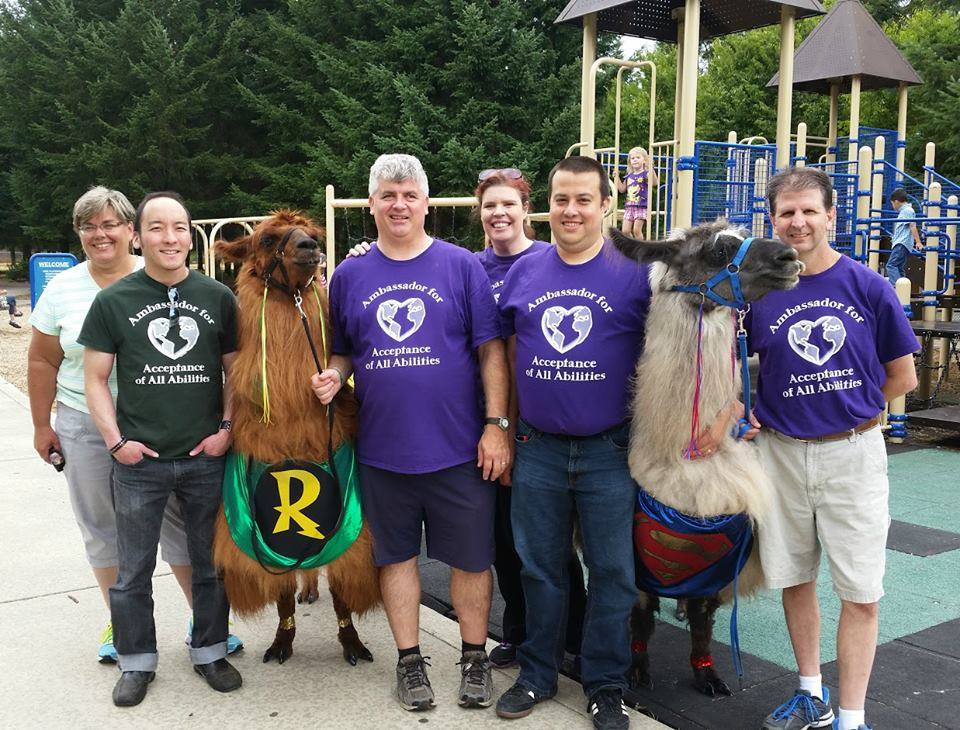 A group photo of SWWADA members, including two llamas in superhero costumes.