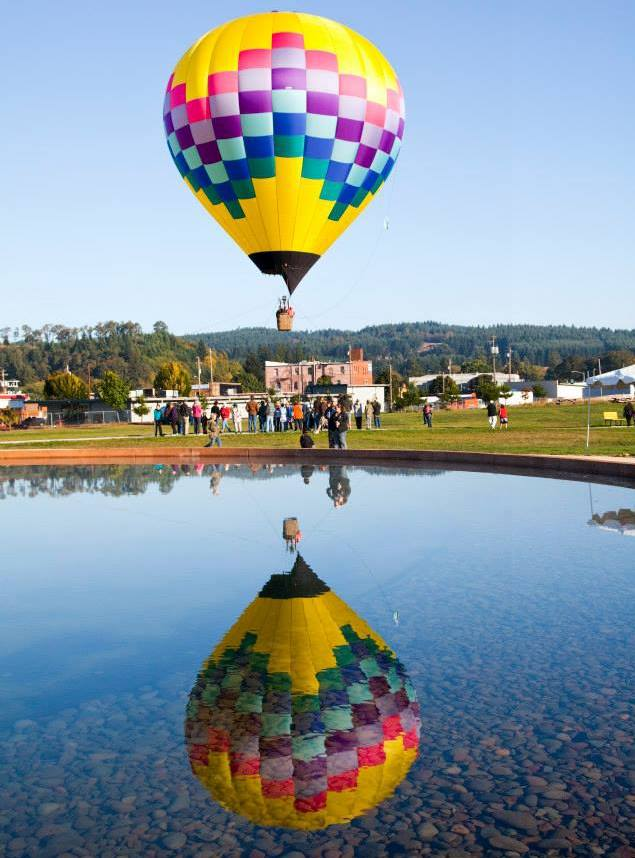 A hot air balloon reflected in a pond.