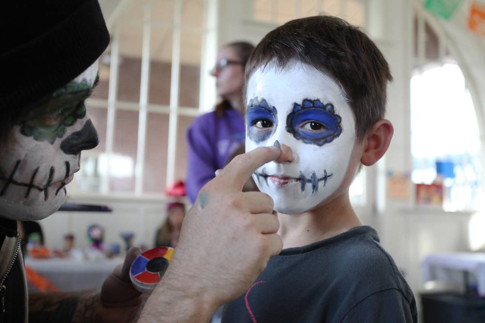 Little boy having his face painted like a sugar skull.