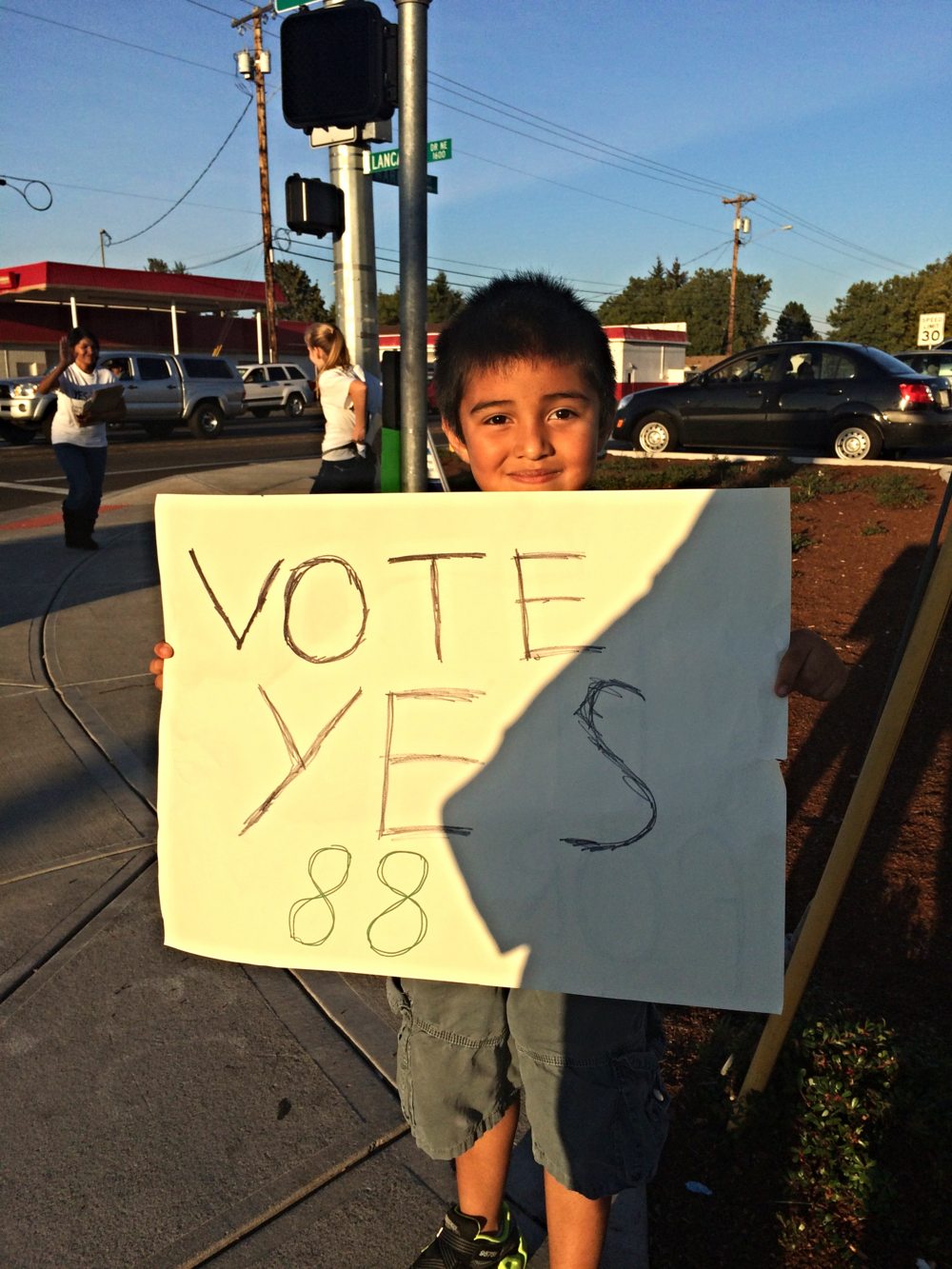 A little boy holding up a sign in support of Measure 88, which would have instituted Driver Cards for undocumented immigrants.