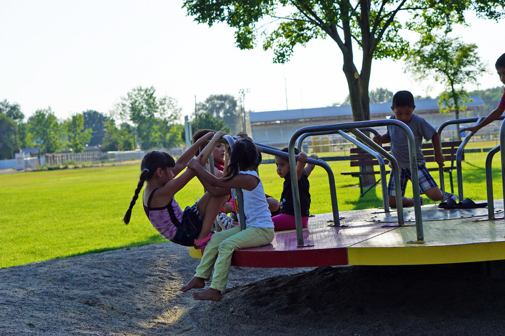 Kids play on a playground carousel.