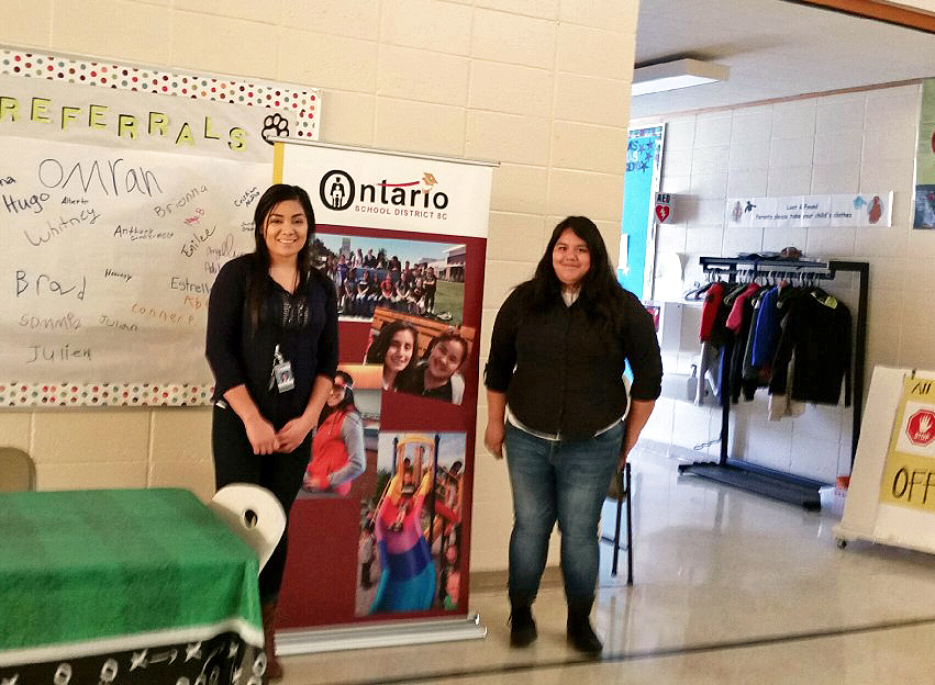 Ontario School District representative Benardina Navarrete and High School Student Genesis Romero stand on either side of an Ontario School District banner in the hallway of Alameda Elementary School.
