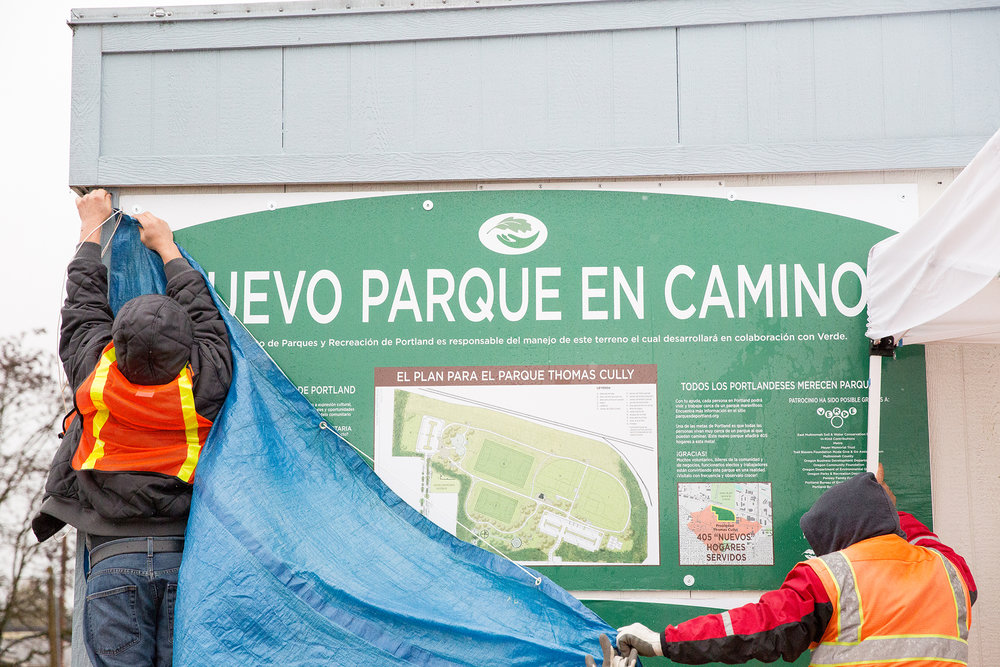 "Two people in orange construction vests hang a tarp over a sign that reads ""¡NUEVE PARQUE EN CAMINO!"" with a map."