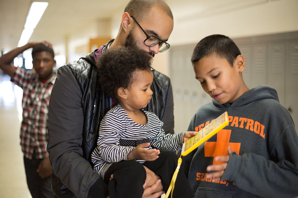 A man holds a toddler in a school hallway. The man, the toddler and a teen standing nearby all look down at a toy the toddler is holding.