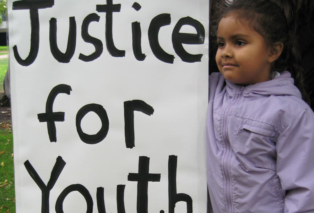 "A child stands next to a picket sign that reads ""Justice for youth."""