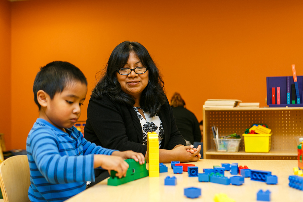 A Latina mother sits beside her son in a classroom while he plays with Legos.