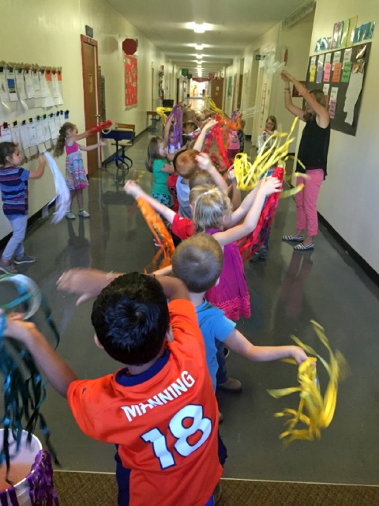 Students play with colorful streamers in a school hallway.