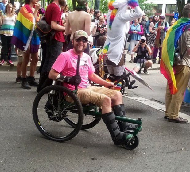 Nico sits in their GRIT Freedom Chair in the middle of a street and smiles. Behind them people wear rainbow flag capes and a unicorn hoodie.