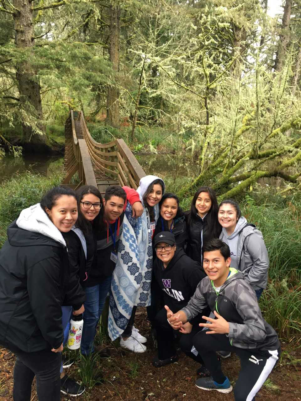 A group of nine Latinx youth pose in front of a wooden bridge surrounded by trees and other greenery.
