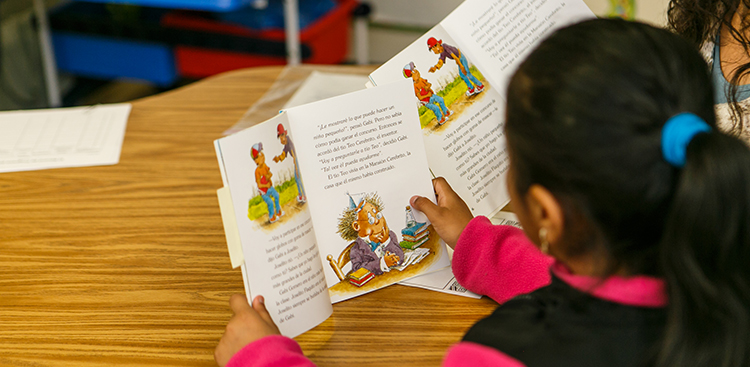 A child reads a Spanish-language picture book
