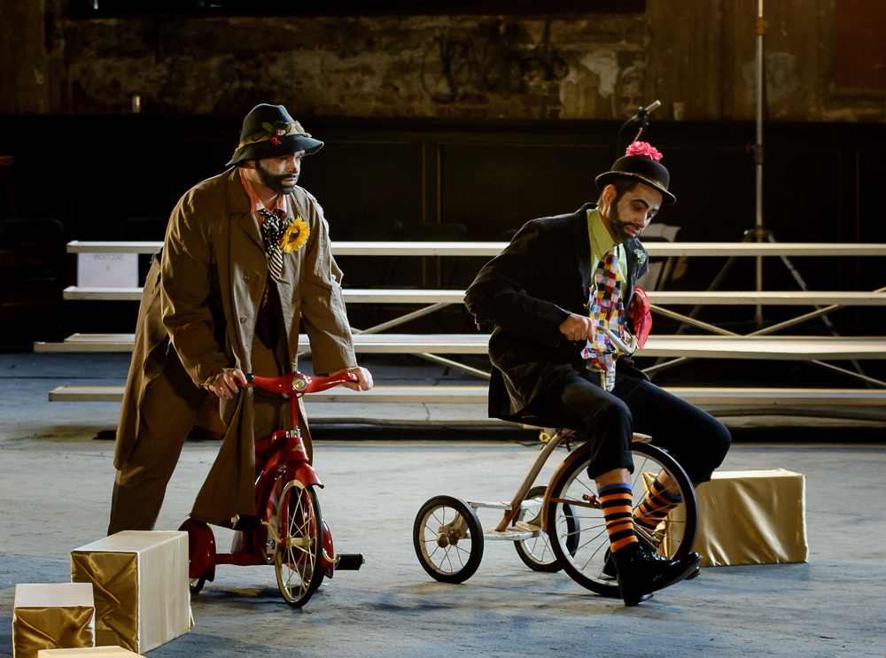 The Doctor (Gregory Purnhagen, right) and his Assistant (Ryan Glover) are transformed into clowns on tricycles.
