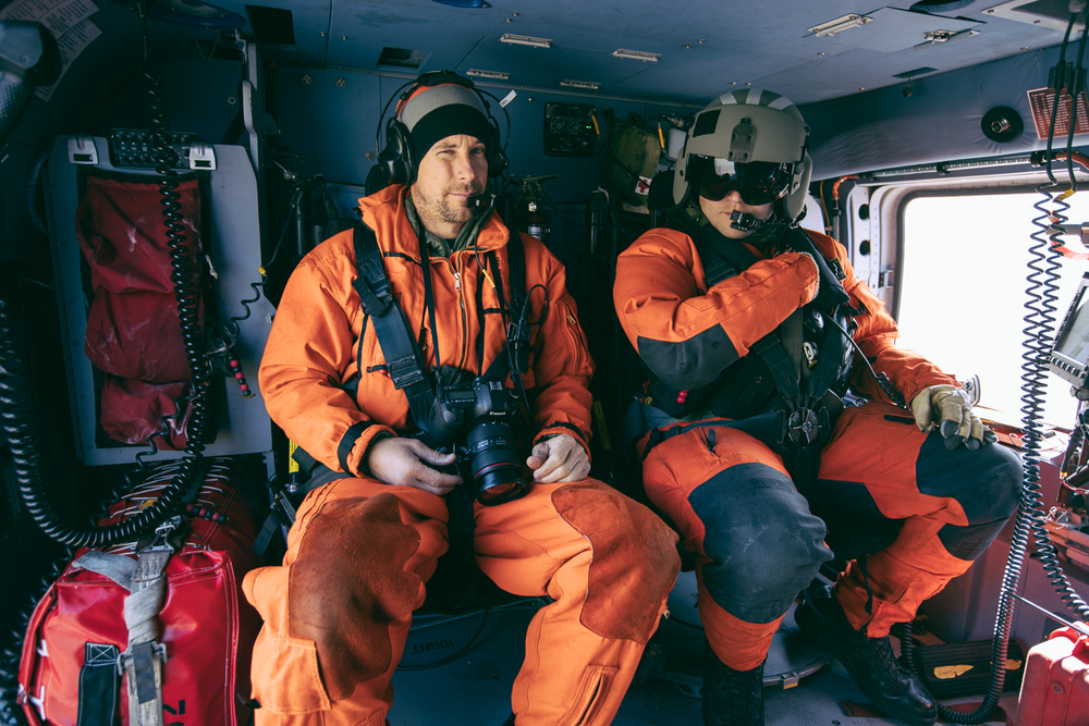 Justin Bastien and Aviation Maintenance Technician Jayson Marrero flying in a USCG Jayhawk helicopter over Chinak Bay, Alaska.