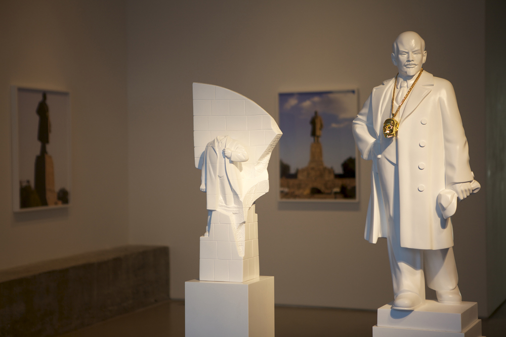 The Propeller Group   Monumental Bling: Lenin East Berlin on Lenin Volgograd [1:25 scale] , 2013 3D printed composite with gold plated pendant and necklace, wood pedestal 68 x 10.5 x 10.5 inches 172.7 x 26.7 x 26.7 cm and 74 x 15.75 x 15.75 inches 188 x 40 x 40 cm