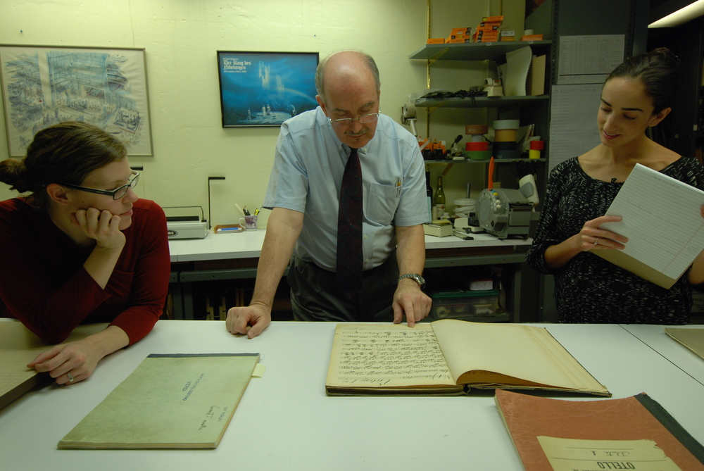 Melissa Robason, Robert Sutherland, and Sarah Vonsattel study an historic violin part of Wagner's Rienzi.