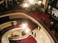 The lobby staircase of the Metropolitan Opera House today, at Lincoln Center for the Performing Arts.  Photo, Wikipedia Commons.
