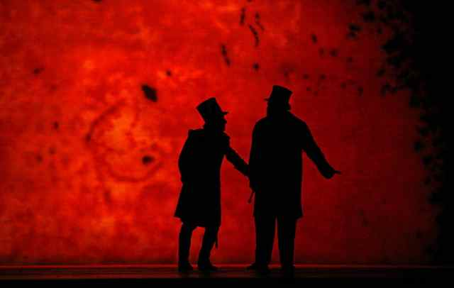 The Captain (left) consults with the Doctor (right) against a blood-red moon in Wozzeck.  Photo by Ken Howard. © 2007 The Metropolitan Opera