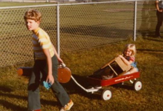 Pete pulling Kari in a wagon at Suzuki camp