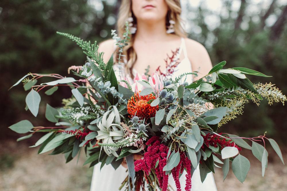 Bohemian style,  wildflower inspired bridal and bridesmaid bouquets with eucalyptus, protea, thistle, astilbe Petal Pushers floral event design studio located in Dripping Springs, Texas.