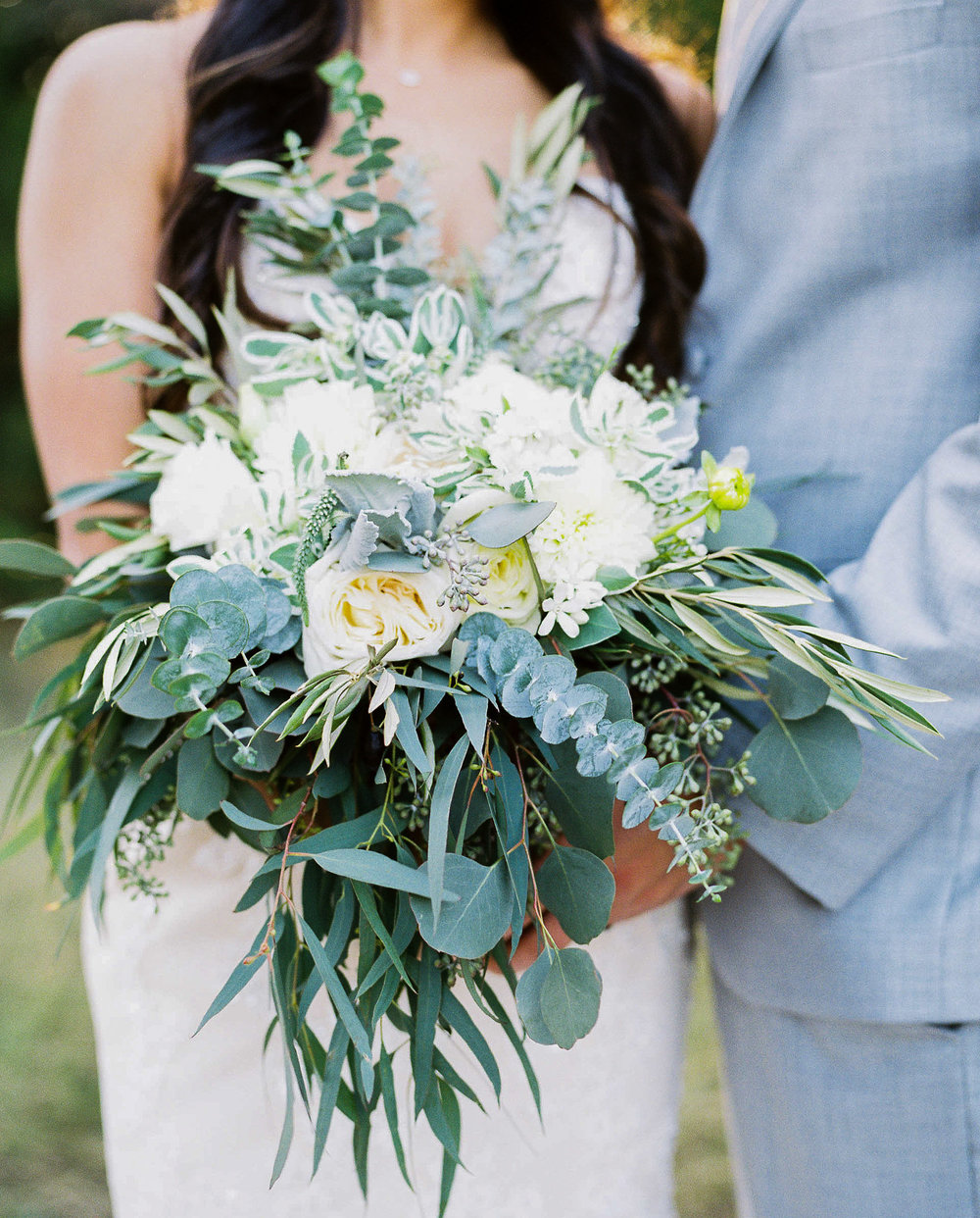 Whimsy and organic inspired bridal and bouquets with white roses, eucalyptus, ranunculus at Vista West Ranch. Petal Pushers floral event design studio located in Dripping Springs, Texas.