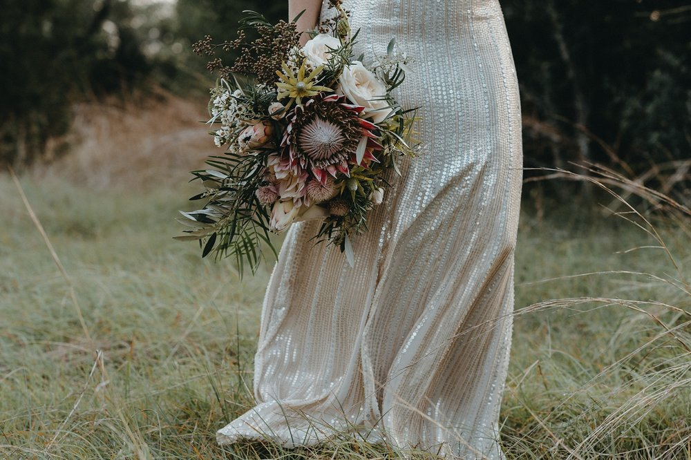Bohemian style, wildflower inspired bridal and bridesmaid bouquets with eucalyptus, protea, peonies at Vista West Ranch. Petal Pushers floral event design studio located in Dripping Springs, Texas.