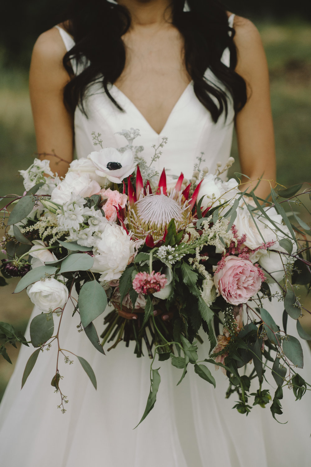 Bohemian style, wildflower inspired bridal and bridesmaid bouquets with Anemone, eucalyptus, protea, peonies at Vista West Ranch. Petal Pushers floral event design studio located in Dripping Springs, Texas.