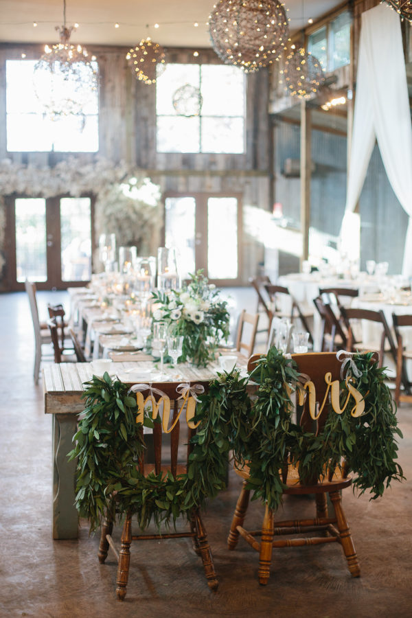 petal-pushers-vista-west-ranch-wedding-hill-country-austin-texas-barn-elegant-florist-reception-decor-rustic-vintage-mr-mrs-sign-chairs-garland