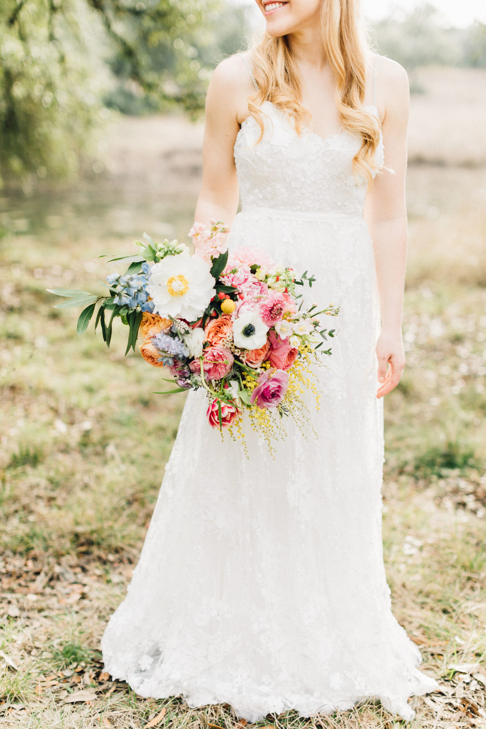 Bohemian style, colorful bridal bouquet with pink, yellow, coral peonies, poppies, anemone, spray roses, ranunculus at Addison Grove. Petal Pushers floral event design studio located in Dripping Springs, Texas.