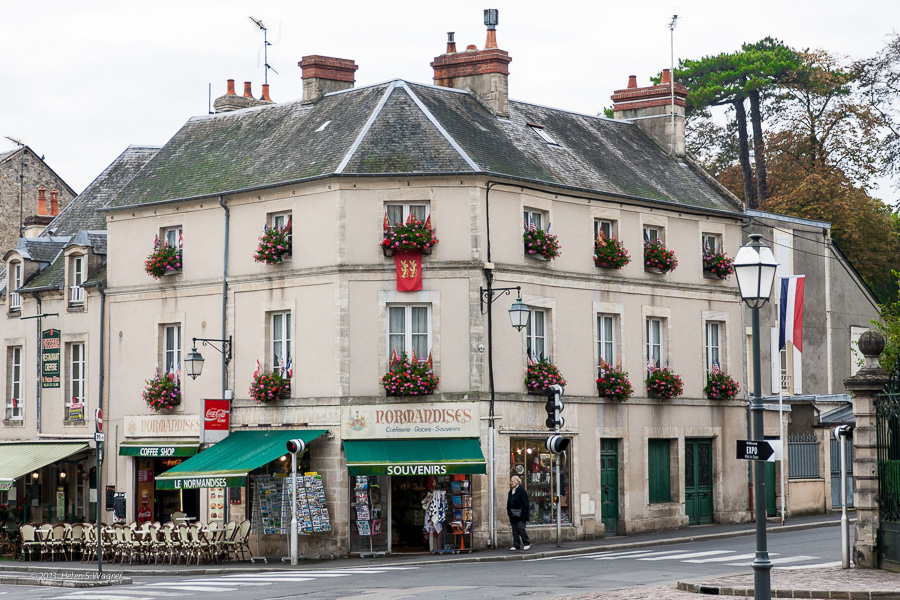 A corner café and market with window boxes adorned with brightly colored flowers was typical of scenes in Bayeux.
