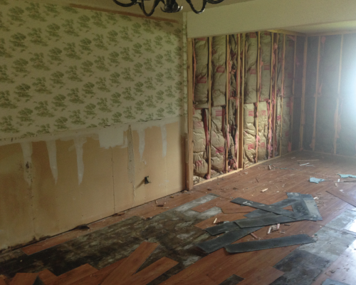 As you can see here, the wood paneling in the living room and the wainscoting in the dining have been removed and the vinyl flooring is in the process of being pulled up.