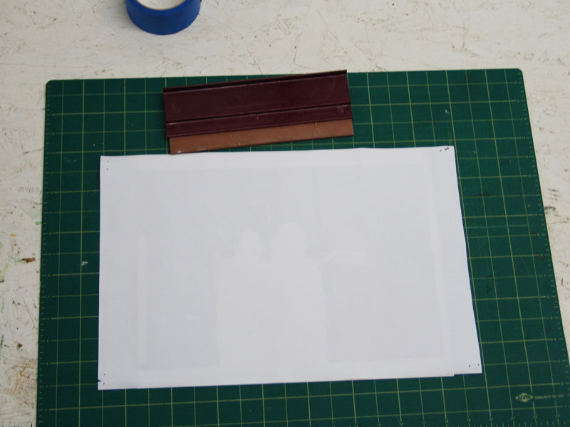 A smooth surface to attach the two pieces of paper. A layer of acrylic medium is painted onto the paper and the photocopy is placed face down.  The air bubbles are removed with the squeegee.  Once this is finished, reattach the image to the wall to dry.