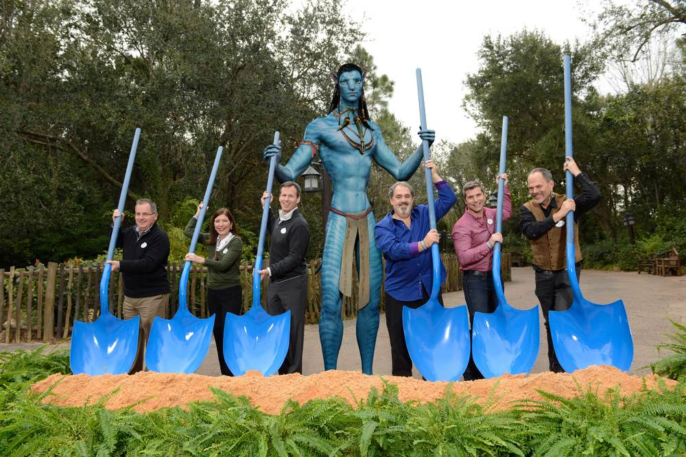 Using Na'vi-inspired shovels and assisted by a Na�vi (photo illustration), (left to right) George Kalogridis, president of Walt Disney World Resort; Meg Crofton, president of Walt Disney Parks and Resorts Operations, United States and France; Tom Staggs, chairman, Walt Disney Parks and Resorts; a Na�vi; Jon Landau, AVATAR Producer; Bruce Vaughn, chief creative executive of Walt Disney Imagineering; and Joe Rohde, creative executive, Walt Disney Imagineering, pose Jan. 8, 2014 during the ceremonial groundbreaking of an AVATAR-inspired land at Disney's Animal Kingdom in Lake Buena Vista, Fla.  The multi-year and largest expansion in Disney�s Animal Kingdom history, the new land will invite Walt Disney World Resort guests to experience the wonders of Pandora when they fly with the banshees, encounter the Na�vi and explore a rich cultural environment with mountains that float and interactive plants that glow at night. (David Roark, photographer)