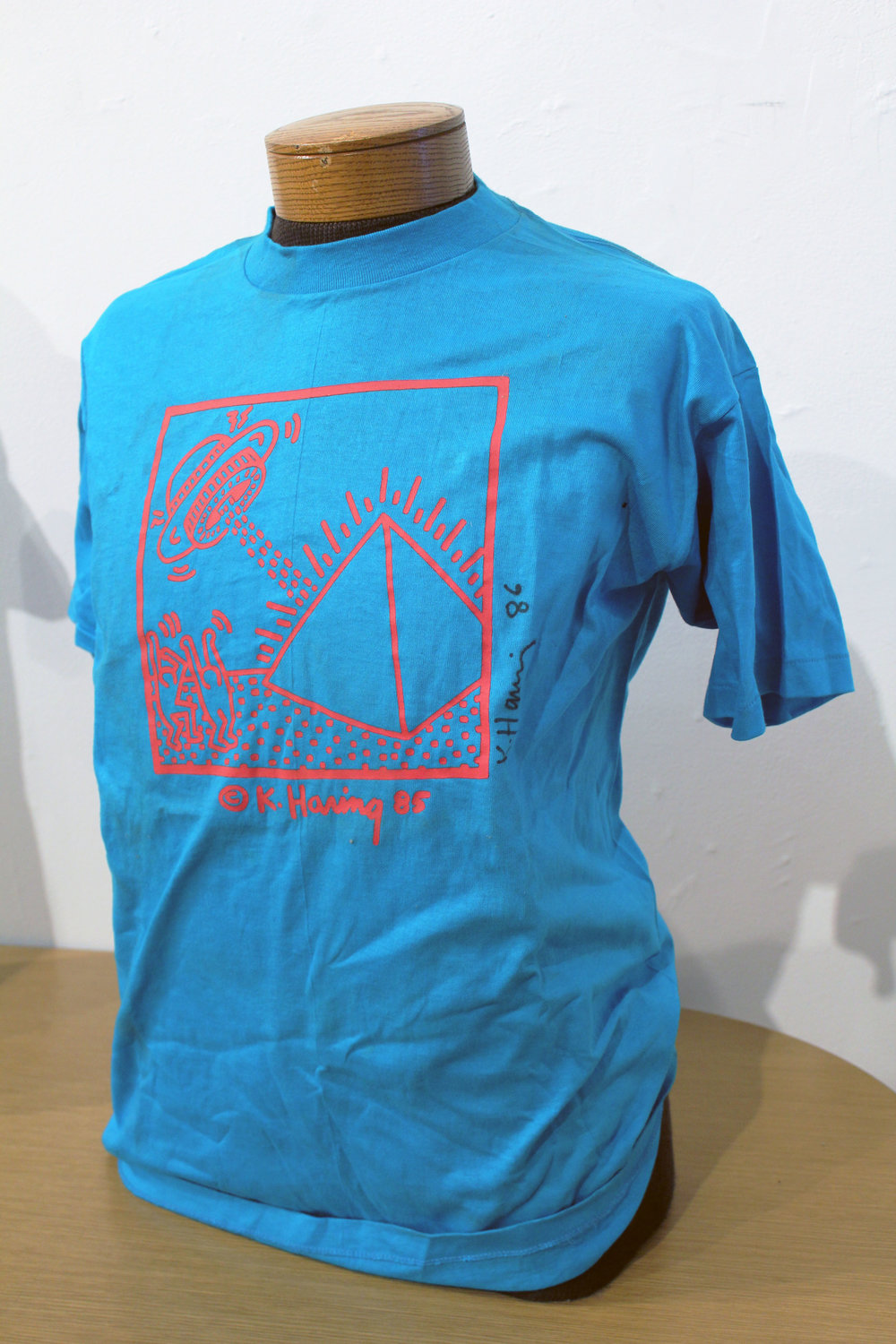 After Keith Haring  Untitled (Shirt Blue), 1985/86 Cotton t-shirt with signature by Keith Haring Signed and dated in ink on recto Size XL Condition: surface dust Estimate: $800/$1,200