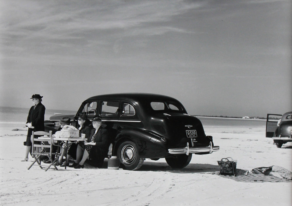 Marion Post Wolcott (1910-1990)    Winter Visitors Picnicking on Running Board of Car on Beach, Sarasota, Florida , 1941/Printed Later Gelatin silver print Signed on verso Image: 8.75 x 12 inches; Framed: 16.5 x 20.5 inches Provenance: Jan Kesner Gallery, Los Angeles, CA Estimate: $1,800/$2,200