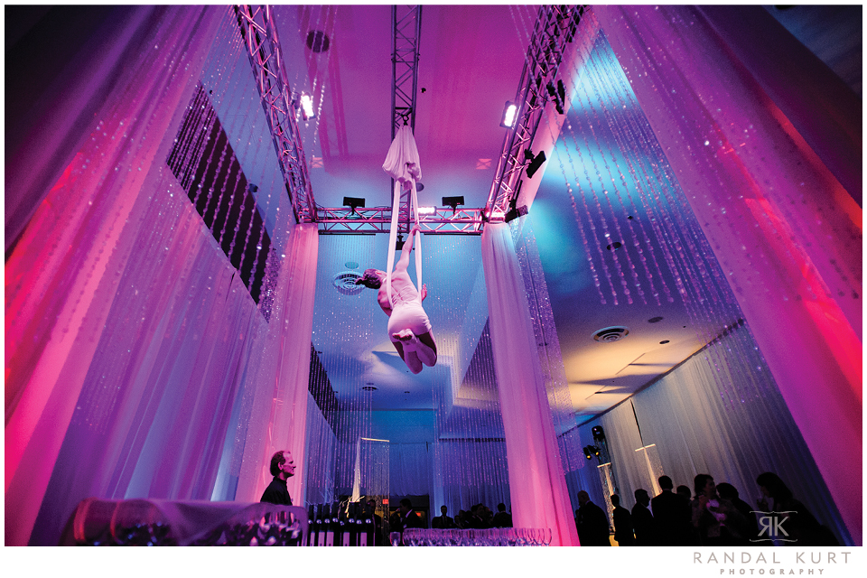 An artist shows her gymnastic skills while pouring wine for guests