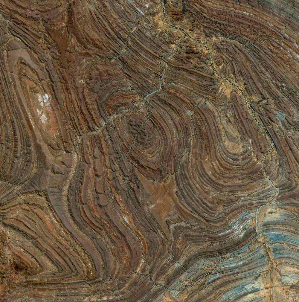 6/15/2015 Adelaide Rift Complex South Australia, Australia -29.791018049°, 137.823068752°   Rock formations of the Adelaide Rift Complex are visible in the South Australian Outback. The swirling patterns are composed of folded and faulted sediments that were deposited there in a large basin more than 540 million years ago. Since then, the land folded and faulted to become a large mountain range and then underwent extensive erosion to become the relatively low ranges that we see today. For a sense of scale, this Overview is approximately 100 square miles.