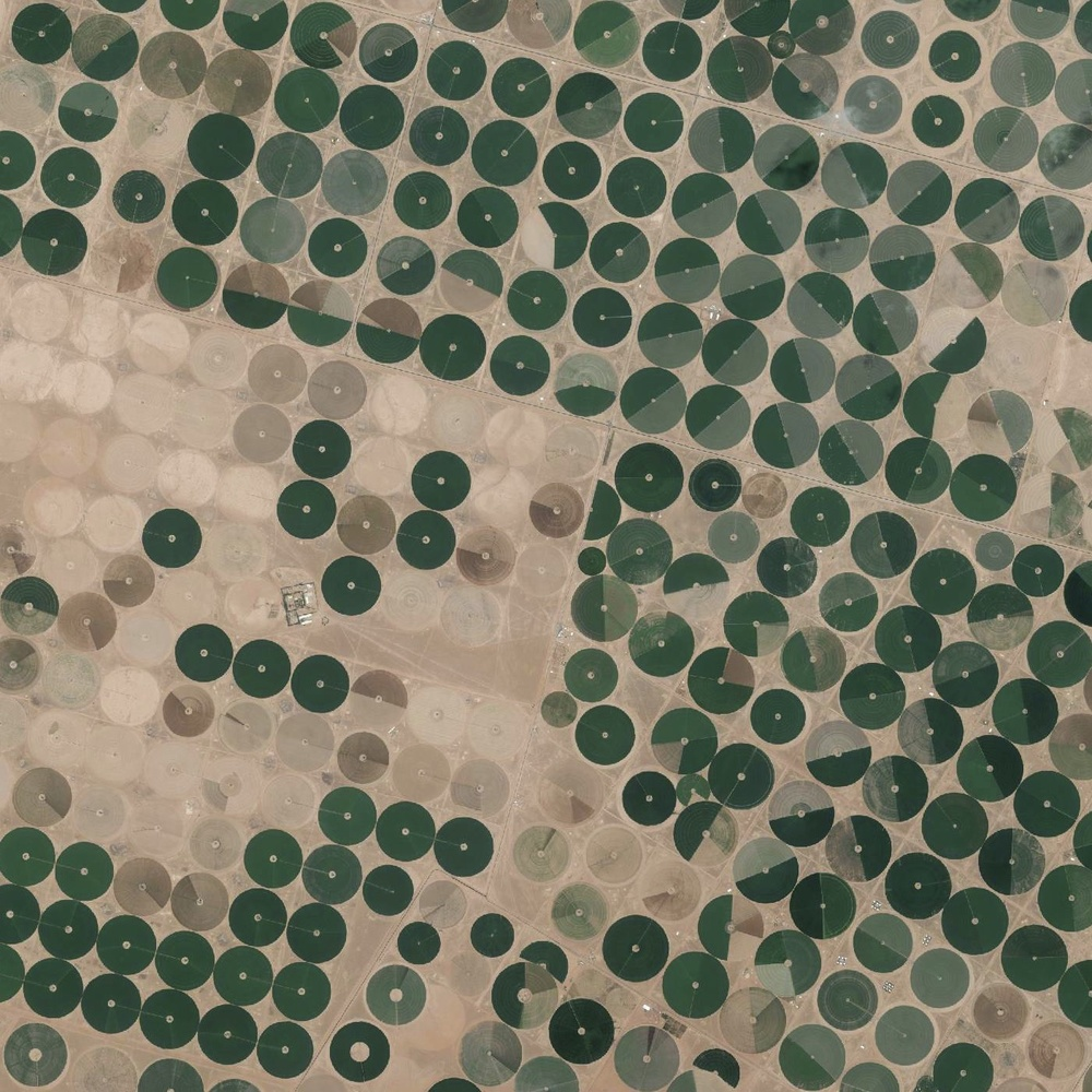 6/16/2015 Center-pivot irrigation Wadi As-Sirhan Basin, Saudi Arabia 30.089890096°, 38.271806556°   Center pivot irrigation is used throughout the Wadi As-Sirhan Basin of Saudi Arabia. Water is mined from depths as great as one kilometer (~3,000 ft), pumped to the surface, and evenly distributed by sprinklers that rotate 360 degrees. Spurred by a government effort to strengthen its agriculture sector, cultivated land in the country grew from 400,000 acres in 1976 to more than 8 million acres by 1993. The diameter of the fields you see here are approximately three kilometers (1.9 miles) across.