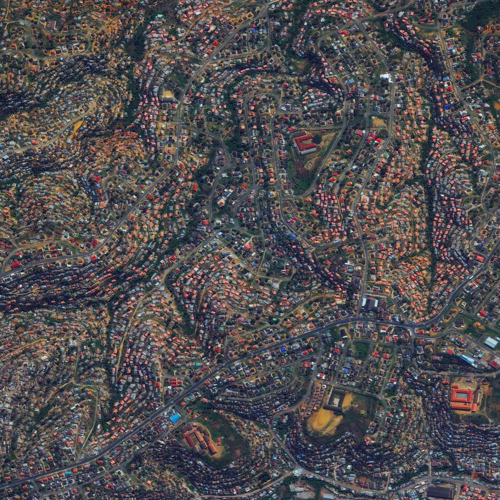10/24/2015 Umlazi Township KwaZulu-Natal, South Africa -29.948412337°, 30.878737128°   Houses swirl on the hills of Umlazi - a township in KwaZulu-Natal, South Africa. The present site of Umlazi was occupied by American missionaries in 1836 and only opened to black residents in 1965, many of whom moved there from Durban. The current population of the township is approximately 405,000.