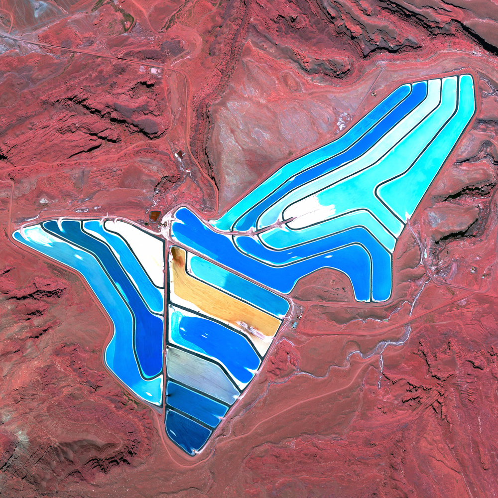 12/15/2015  Potash evaporation ponds  Moab, Utah, USA  38.483377775°, -109.681333272°     Blue evaporation ponds are visible at the Intrepid Potash Mine in Moab, Utah, USA. The mine produces muriate of potash, a potassium-containing salt used widely by farmers in fertilizer. The salt is pumped to the surface from underground brines and dried in massive solar ponds that vibrantly extend across the landscape. As the water evaporates over the course of 300 days, the salts crystallize out. So why are you seeing such vibrant colors? The water is dyed bright blue to reduce the amount of time it takes for the potash to crystallize; darker water absorbs more sunlight and heat.