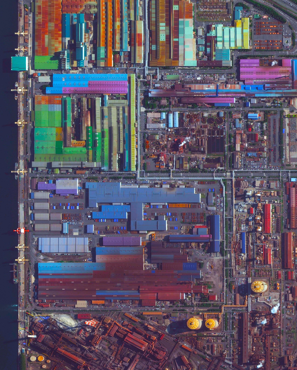 2/1/2016  Industrial buildings  Tokai, Japan  35.039460°, 136.889525°     Colorful, metal-roofed industrial buildings line the coast of Tokai, Japan. The city's economy is dominated by a massive steel mill - a portion of which is seen at the bottom of this Overview. Nippon Steel, the company that owns the mill, has an annual production of more than 47 million tons of steel across its various facilities. Steels - consisting of alloys of iron and other elements, primarily carbon - is a major component in buildings, infrastructure, tools, ships, automobiles, appliances, and weapons.