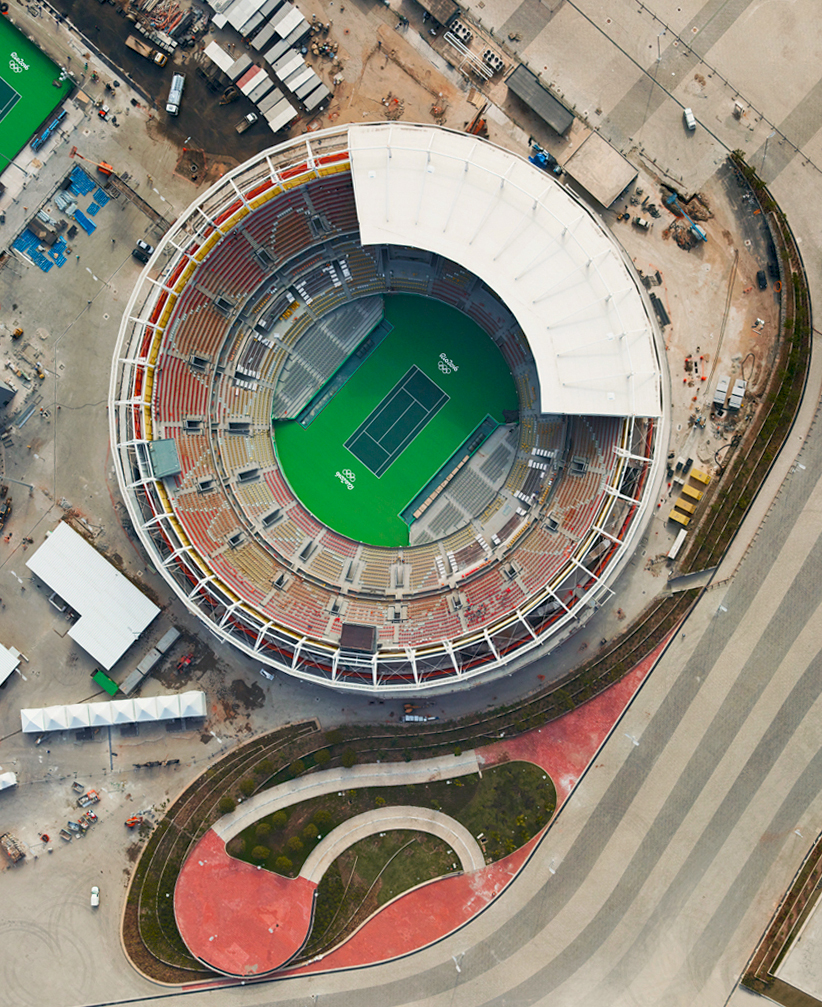 8/5/2016 Olympic Tennis Center Rio de Janiero, Brazil 22.978822°S 43.396382°W   The opening ceremony of the XXXI Olympiad will take place tonight in Rio de Janeiro, Brazil. The city's newly constructed Olympic Tennis Center and Maria Esther Bueno Court are seen in this shot from aerial photographer @gilesinfo. This particular photo is taken from Morar Olimpíadas, his new book that examines the physical transformation of Rio de Janeiro in the run up to the event. Let the games begin!
