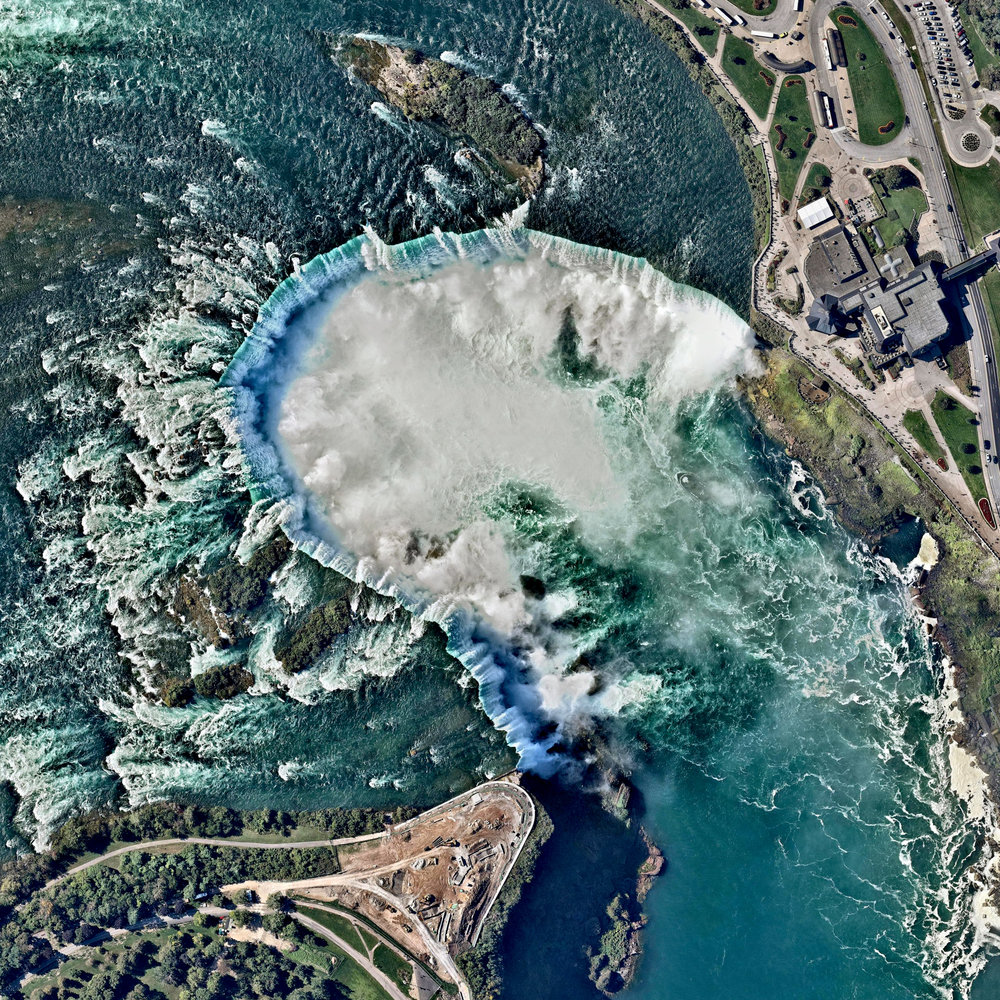 10/3/2016 Niagara Falls Canada / United States 43.077305°N 79.07562°W   Niagara Falls is the collective name for three waterfalls that straddle the border between Ontario, Canada and the United States. Horseshoe Falls is seen here. The falls have the highest flow rate of any waterfall in the world, with a vertical drop of more than 165 feet (50 m). The Maid of the Mist, also visible here, is a boat that has carried passengers into the rapids below the falls since 1846.   Source imagery: NearMap