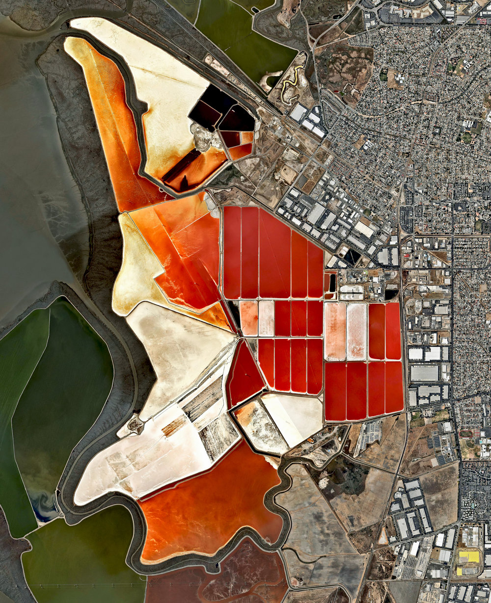 10/10/2016 Salt ponds San Francisco Bay, California, USA 37.5106531, -122.053325   The salt evaporation ponds seen here cover roughly 10 square miles (26 square km) in San Francisco Bay, California, USA. Salt is extracted from the water here through a lengthy process. First, water from the bay is channeled into massive basins where it begins a transformation into brines. Over five years, the brines evaporate, concentrate, and travel several miles before they are collected as pure salt crystals. The massive ponds get their vibrant color from a particular species of algae (Dunaliella) that thrives in extremely salty water and produces a red pigment. Source imagery: Nearmap