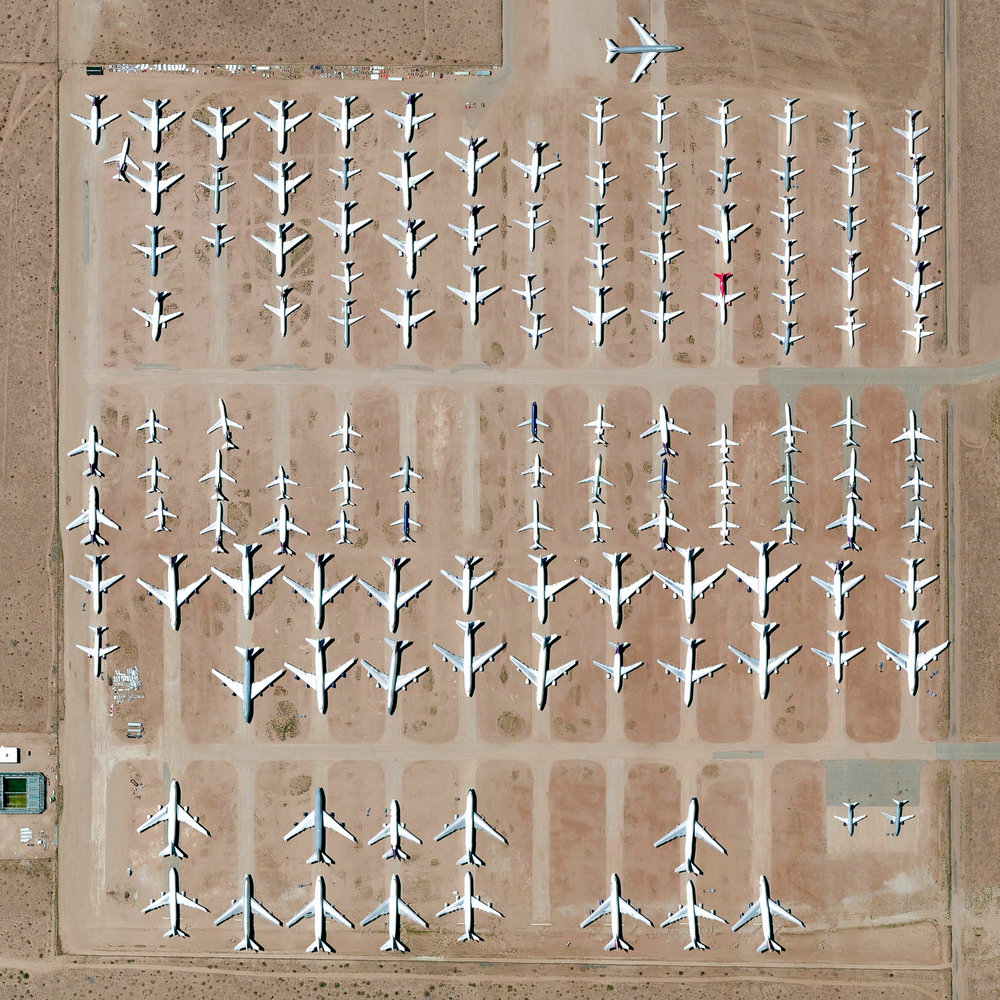 "10/19/2016 Southern California Logistics Airport Victorville, California, USA 34°35′51″N 117°22′59″W   Here's one of my favorite images from the Where We Waste chapter of ""Overview"". The Southern California Logistics Airport in Victorville, California contains an aircraft boneyard with more than 150 retired planes. Because the demand for jumbo jets has dropped significantly in the last two decades in favor of smaller, more affordable twin‑engine planes, many large aircrafts such as Boeing 747s have been retired. The dry conditions in Victorville – located on the edge of the Mojave Desert – limits the corrosion of metal, meaning planes can be stored here for years while they are stripped for spare parts."