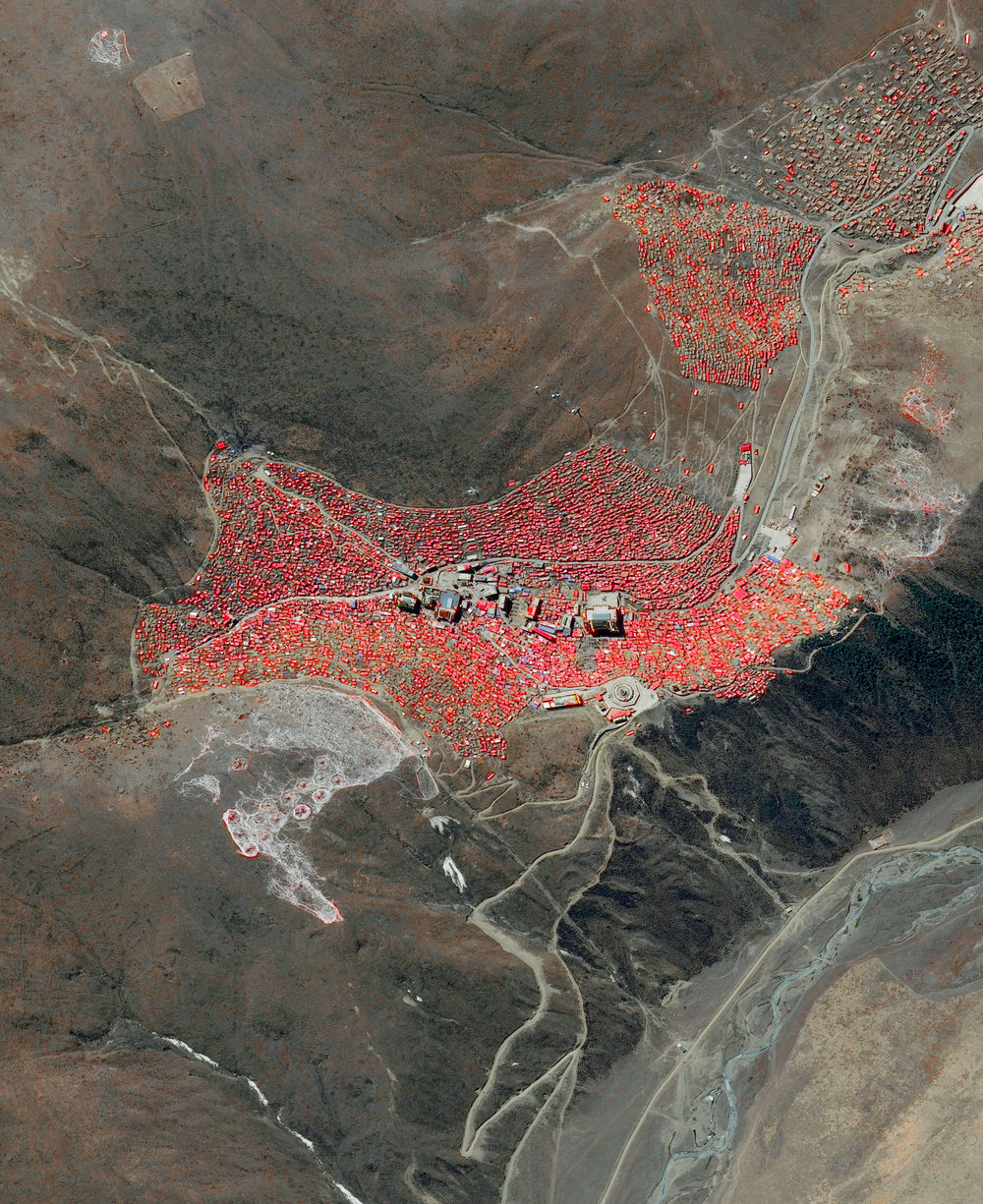 11/29/2016 Larung Gar Tibet 32.1356°N 100.4565°E   Hundreds of dwellings - all painted in a vibrant red color - make up Larung Gar, the world's largest Buddhist institute. The settlement is located in a remote valley in Tibet and contains a population that has grown to approximately 20,000 people since its founding in 1980. In recent years, the Chinese government has started to systemically demolish homes and force thousands of occupants out of Larung Gar, claiming the settlement is too crowded and unsafe. They have also closed off the area to all foreigners. Many Tibetans fear the erosion of their language, traditions, and ways of worship in the midst of these incursions by the Chinese government.