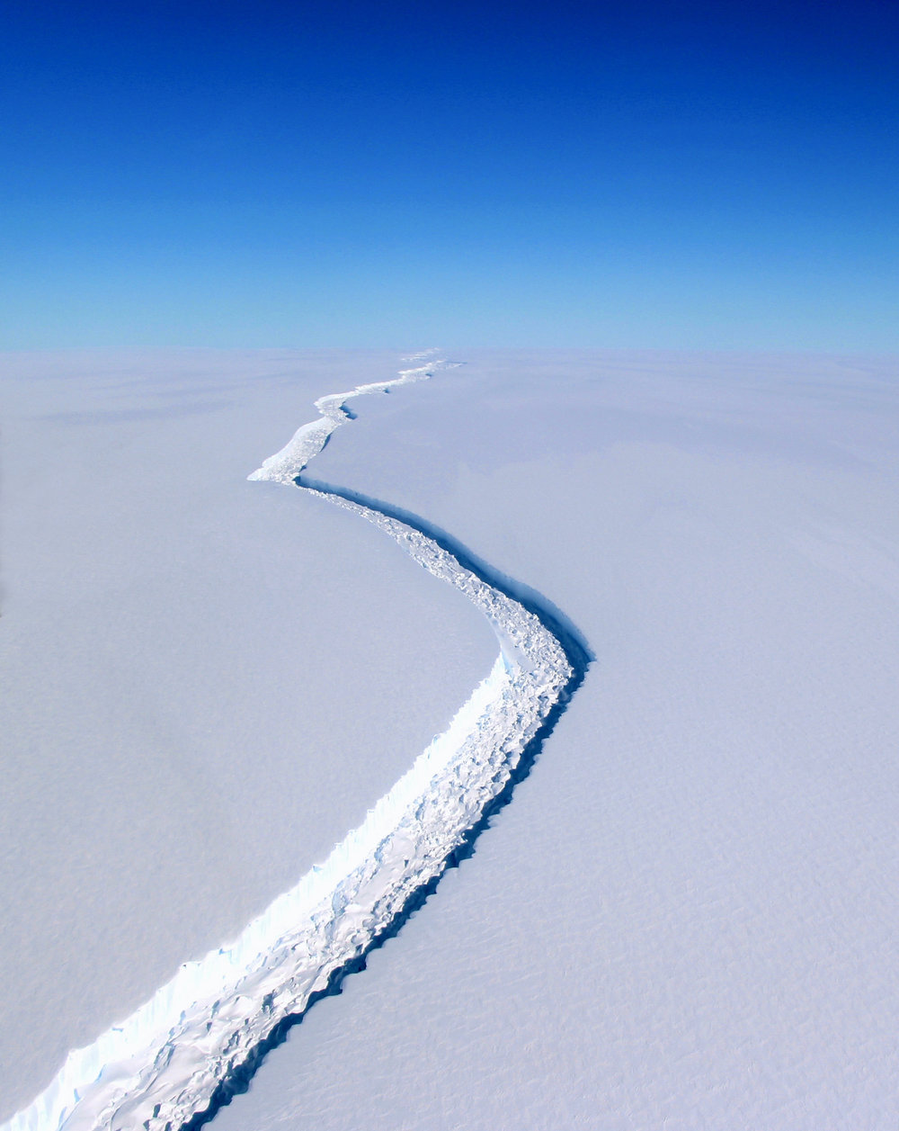 A newly formed crack in the Larsen Ice Shelf in Antarctica extends as far as the eye can see. The fracture is currently measured at 100 feet wide and over 100 miles long, growing more than 50 miles alone since 2011. If this chunk of ice breaks away, roughly 2,000 square miles will be lost - that's roughly the size of the state of Delaware. The break is the latest example of major ice loss in the fast warming Antarctic Peninsula and could lead to a rise in global sea levels by roughly four inches (10 centimeters).  Photo taken from airplane by John Sonntag for NASA