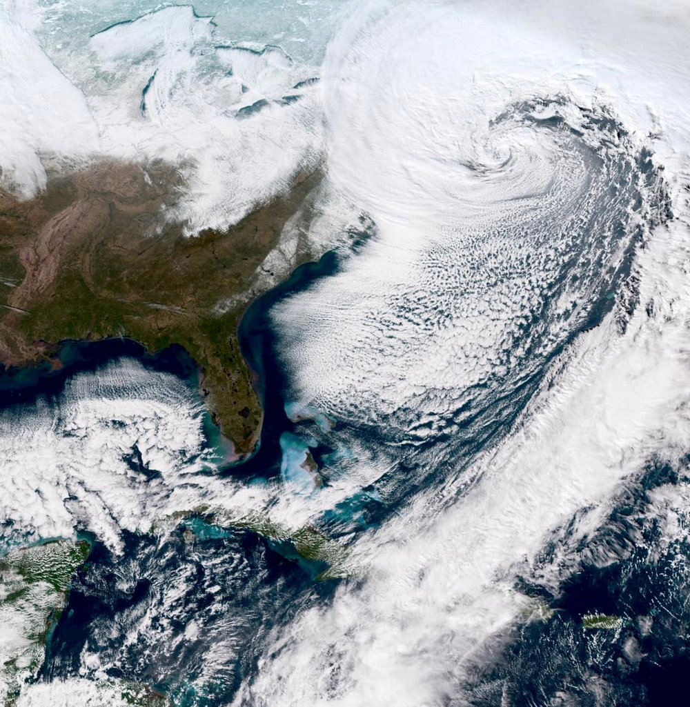 "Check out this incredible view of the ""Bomb Cyclone"" - the powerful winter storm currently making its way toward the northeastern United States. From this vantage point in outer space, we can see the center of the low pressure area and a thick band of clouds bringing even more snow and gusty winds from the Mid-Atlantic states towards New England. The term ""bomb cyclone"" refers to the intensification of the storm that happens when an extreme drop of pressure occurs in a short period of time."